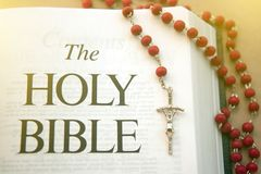 Wooden rosary with a crucifix between the pages of the Bible Royalty Free Stock Images