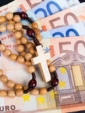 Wooden rosary on Euro banknotes Stock Photo