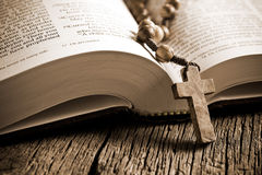 Wooden rosary on the open Bible Stock Images