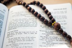 Wooden rosary between the pages of the Bible with the psalm Royalty Free Stock Images