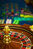 Wooden roulette wheel. Closeup of a wooden roulette wheel, with betting chips behind royalty free stock image