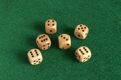 Wooden dice set on green felt cloth. Wooden round corner dice six sided dots set for playing on dark green poker table felt cloth surface as background Stock Image
