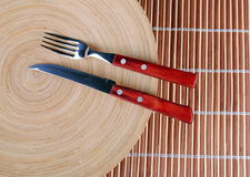 Wooden round dish and red cutlery Royalty Free Stock Image