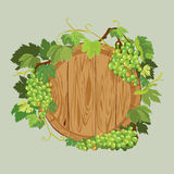 Wooden round frame with green grapes and leaves  on beig Stock Photography