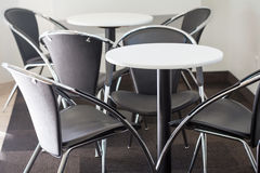 Wooden round table with chairs. In background Stock Photography