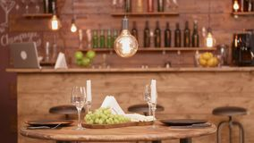 A wooden round table in an empty restaurant with cheese and grape appetizer. Empty restaurant before a date stock video footage
