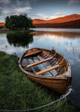 Wooden row boat on the lake stock images