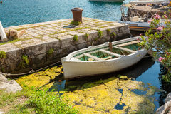 Wooden rowboat mooring at pier at sunny day Royalty Free Stock Photo