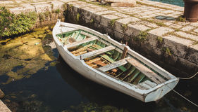 Wooden rowboat mooring to ancient stone berth Stock Images