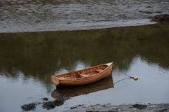 Wooden Rowboat in Shallow Waters. A wooden rowboat is left anchored in shallow waters resulting from drought stock images