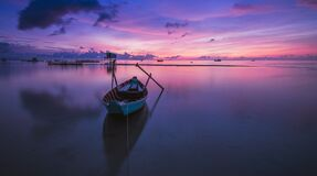 Wooden rowboat in still waters at sunset Stock Image