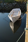 Wooden rowing boat. White wooden rowing or fishing boat moored by pier and reflecting on water Royalty Free Stock Image