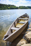 Wooden rowing boat on lake shore Stock Photography