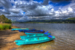 Wooden rowing boats by lake with mountains and blue sky the Lake District Cumbria England UK in HDR like painting. Wooden rowing boats by a lake with mountains Royalty Free Stock Photo