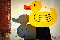 Wooden Rubber Duck with Shadow on Building. A yellow and orange rubber duck made out of wood and a shadow casting on a building in Delevan, Wisconsin Stock Photography