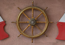 Wooden rudder. Marine steering wheel on a stone wall Stock Photography