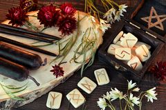 Wooden runes and black candles on witch table. Wicca, esoteric, divination and occult concept with vintage magic objects for mystic rituals, Halloween royalty free stock image