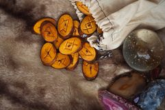 Wooden runes on the fur. Wood runes handmade fur are lying beside the crystal ball and semi-precious stones Stock Photos