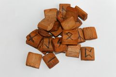 Wooden runes lie on a table on a white background.  Royalty Free Stock Images