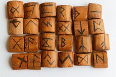 Wooden runes lie on a table on a white background.  Stock Photos