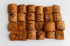 Wooden runes lie on a table on a white background.  Royalty Free Stock Image