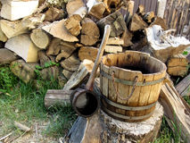 A wooden rural vintage bucket and a ladle on the background of a pile of firewood Royalty Free Stock Photo