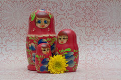 Wooden Russian Matryoshka Dolls. Three wooden nesting Matryoshka Dolls with flower on lace background Royalty Free Stock Photography