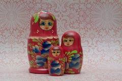 Wooden Russian Matryoshka Dolls. Three wooden nesting Matryoshka Dolls on lace background Stock Photography