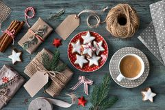 Wooden rustic background with cup of coffee and wrapping of Chri Stock Images