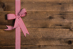 Wooden rustic background with a red white checkered ribbon. Stock Photos