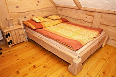 Wooden rustic bed. Wooden rustic bed in country cottage bedroom Royalty Free Stock Photography