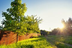 Wooden rustic fence in village and sunset Stock Images