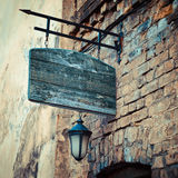 Wooden rustic signboard on aged medieval wall Royalty Free Stock Images