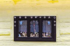 Wooden, rustic window in old cottage, Vlkolinec, Slovakia. Wooden, rustic window in cottage on yellow wall Stock Image
