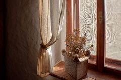 Wooden rustic window with rural country stone pot of dry poppies plants on a wooden window sill in the bright morning sunlight royalty free stock images