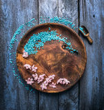 Wooden rustical bowl with sea salt, scoop and flowers on blue table, wellness background, top view Royalty Free Stock Images