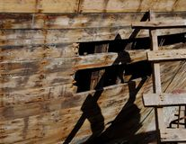 Wooden rusty hole on a small boat with ladder stock photo