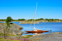 Wooden sailboat in natural harbour Royalty Free Stock Images