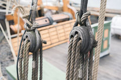 Wooden sailboat pulleys and ropes detail. Ancient wooden sailboat pulleys and ropes detail stock photo