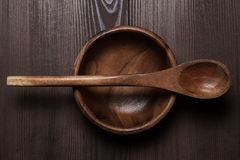 Wooden salad plate and spoon on brown table Stock Photography