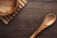 Wooden salad plate and spoon on brown table Royalty Free Stock Photo