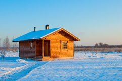 Wooden saun house in snow and frozen landscape Stock Photos