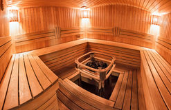 Wooden sauna. Light wooden sauna with bench and hot stones Royalty Free Stock Photos