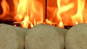 Wooden sawdust briquettes straightened, background burning fire. Alternative fuel, bio fuel. Slider shot. stock footage