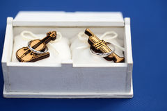 Wooden saxophone and violin in box. Closeup view of small wooden musical instrument of violin and saxophone lying in white box with silver ring on blue Royalty Free Stock Image