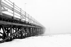 Wooden scary bridge disappearing in the fog. Bridge leading to nowhere. Stock Photo