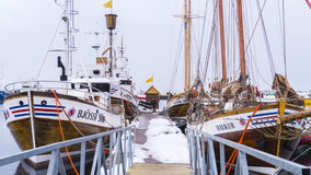 Wooden Schooner Boats Docked along a Snowy Wooden Pier. Royalty Free Stock Photo
