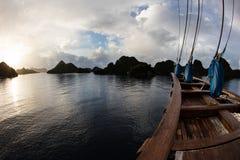 Wooden Schooner and Limestone Islands in Raja Ampat Stock Image