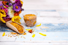 Wooden scoop with bee pollen and plastic glass with pollen. On the table stock photography