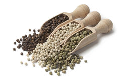 Wooden scoops with black, white and green peppercorns Royalty Free Stock Photos